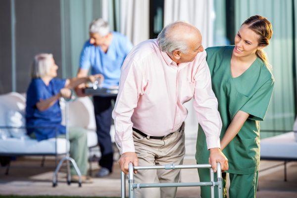 Verpleegster helpt man met rollator